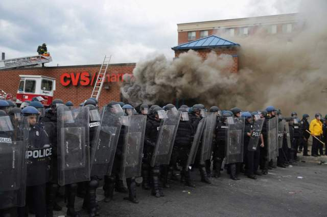 BALTIMORE, MD - APRIL 27: Baltimore Police form a parimeter around a CVS pharmacy that was looted and burned near the corner of Pennsylvania and North avenues during violent protests following the funeral of Freddie Gray April 27, 2015 in Baltimore, Maryland. Gray, 25, who was arrested for possessing a switch blade knife April 12 outside the Gilmor Homes housing project on Baltimore's west side. According to his attorney, Gray died a week later in the hospital from a severe spinal cord injury he received while in police custody.  (Photo by Chip Somodevilla/Getty Images)